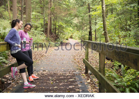 Mother and daughter water bottles taking break woods - Stock Photo