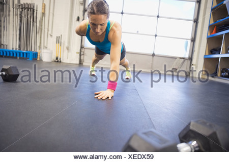 Determined woman doing one arm push-ups in gym - Stock Photo