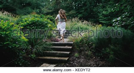 Rear view of young woman running up steps in a garden - Stock Photo