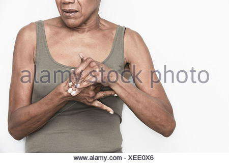 Cropped portrait of senior woman with hands clasped - Stock Photo