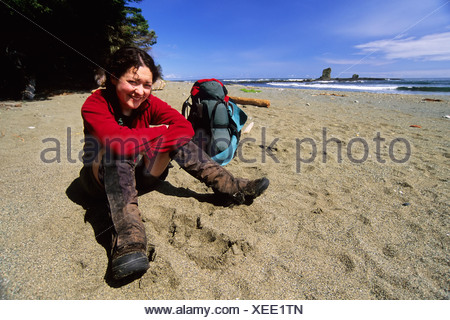 A Young Woman (20-25) takes a break from hiking along a beach section of the West Coast Trail near Carmanah Creek in Pacific Rim - Stock Photo