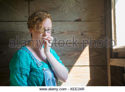 Portrait of a girl with curly red hair and eyeglasses standing against an old, wooden barn wall; Pittsboro, North Carolina, USA - Stock Photo