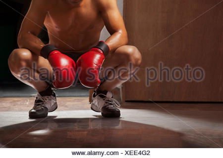 Low section of man wearing boxing gloves crouching in gym - Stock Photo