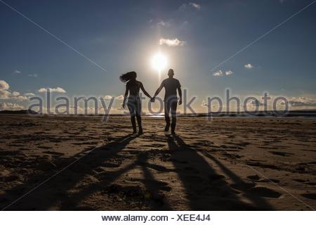 Silhouette of a couple walking along beach holding hands - Stock Photo