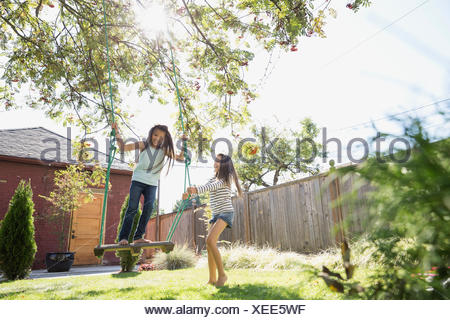 Sisters playing on tree swing in backyard - Stock Photo