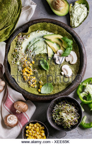 Green spinach matcha tortilla with vegan ingredients for filling. Sweet corn, avocado, green paprika, sprouts, mushrooms served in terracotta plate ov - Stock Photo