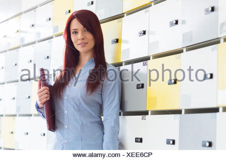 Portrait of beautiful businesswoman with file standing in locker room at creative office - Stock Photo