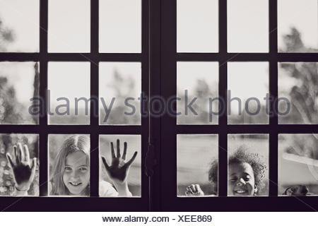 Two girls looking through a window - Stock Photo
