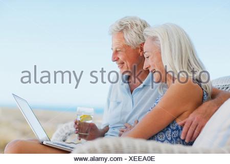 Senior couple using laptop on patio - Stock Photo