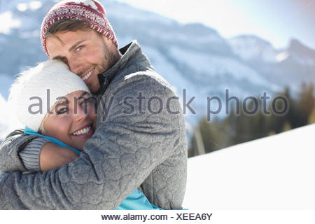 Portrait of smiling couple hugging in snow - Stock Photo