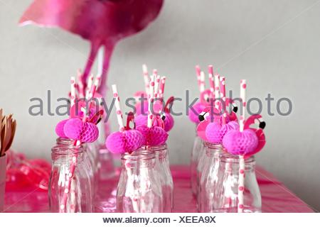 Pink flamingo straws in glass bottles in a row