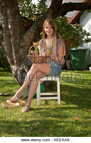 Mid adult woman sitting next to apple tree in the garden, Munich, Bavaria, Germany - Stock Photo