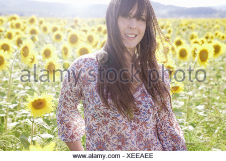 Mid adult woman in field of sunflowers - Stock Photo