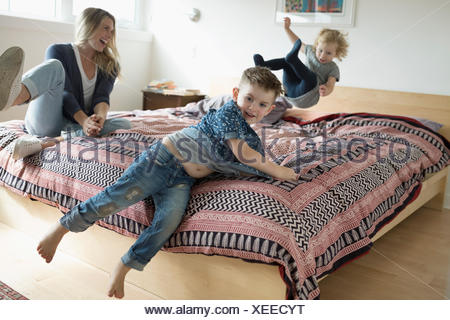 Mother and toddler daughter and son playing, jumping on bed - Stock Photo