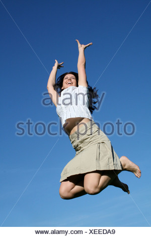 Low angle view of young woman jumping in mid-air - Stock Photo
