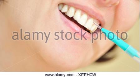 woman cleaning her teeth with an interdental brush. - Stock Photo