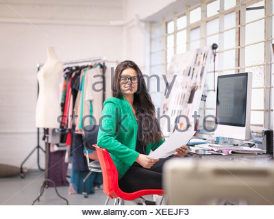 Fashion designer working at computer in fashion design studio, portrait - Stock Photo