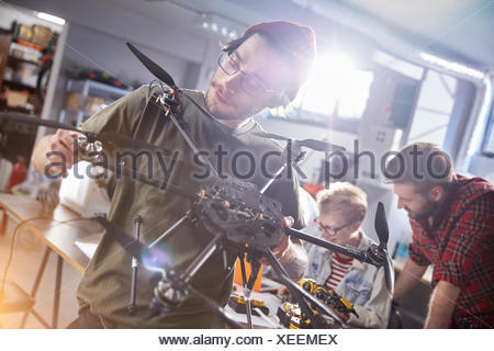 Male designer assembling drone in workshop - Stock Photo