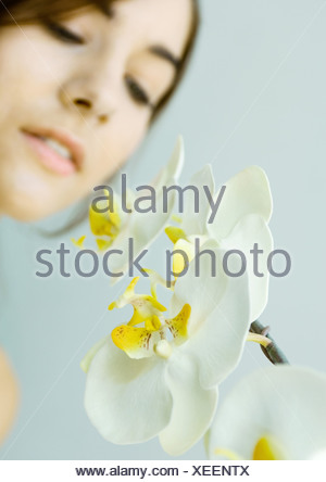 Woman looking at orchid - Stock Photo