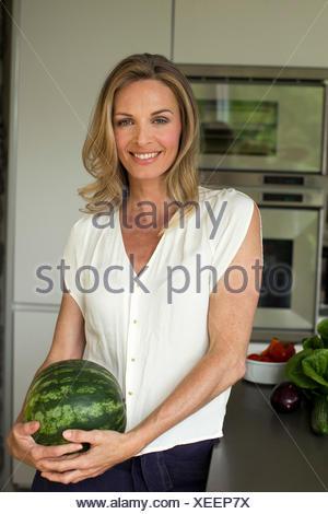 Mature woman holding watermelon - Stock Photo