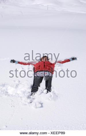 girl lying in snow - Stock Photo