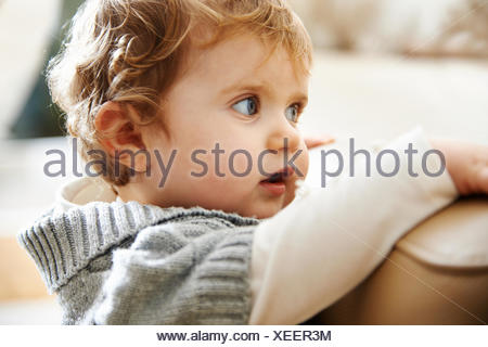 Baby girl clinging to edge of sofa - Stock Photo