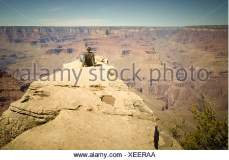 Rear view of a young man sitting on ledge, grand canyon, arizona, america, USA - Stock Photo
