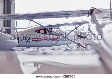 Small airplane in hangar - Stock Photo