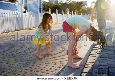 Two little girls are playing football in an alleyway with the sun in background. - Stock Photo