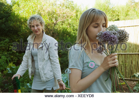 Young woman smelling flowers in garden - Stock Photo