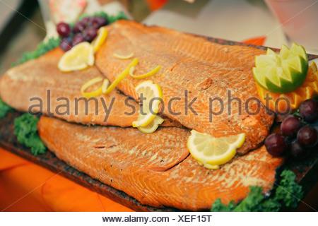 fish garnished with lemon slices on a board; gresham, oregon, united states of america - Stock Photo