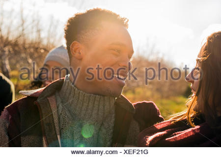 A group of three friends outdoors on a winter walk. - Stock Photo