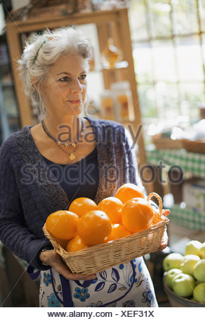 Organic Farmer at Work A woman carrying a box of large oranges - Stock Photo
