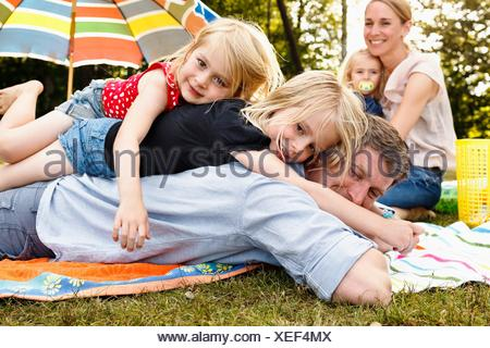 Two daughters lying on top of father at family picnic in park - Stock Photo
