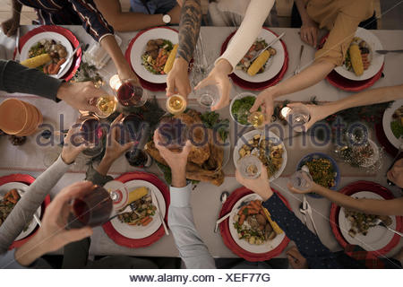 Overhead view family toasting wine glasses at candlelight Christmas turkey  dinner at table - Stock Photo