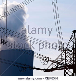 power pole with high voltage power lines and industry, Germany, North Rhine-Westphalia - Stock Photo