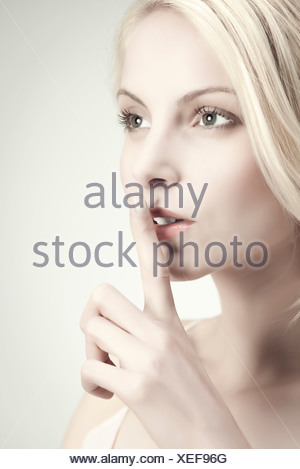 Young woman with finger on lips - Stock Photo