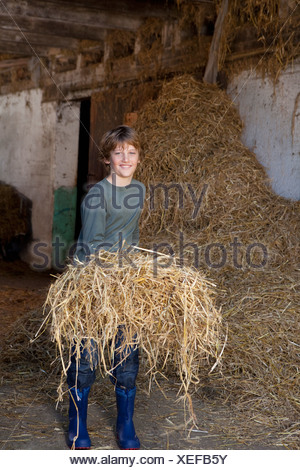 Boy with hay on fork, smiling - Stock Photo