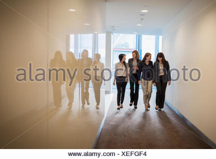 Businesswomen walking in a row in office corridor - Stock Photo