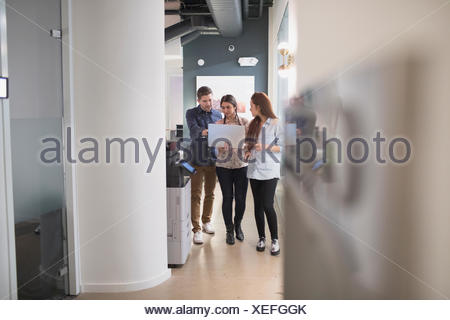 Young professionals working on laptop in office - Stock Photo