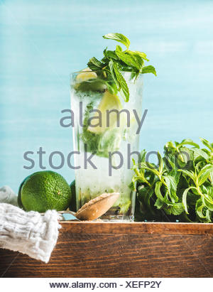 Homemade Mojito cocktail in tall glass served with bunch of mint, brown sugar and limes on wooden board. Turquoise blue backgrou - Stock Photo