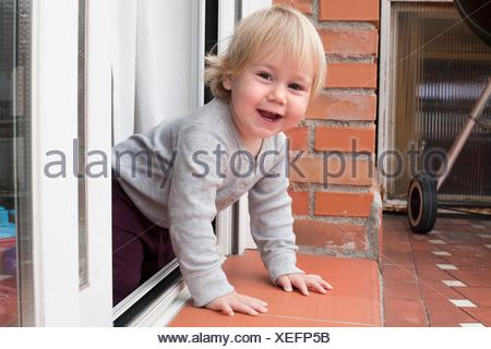portrait of blonde caucasian baby nineteen month age chubby face looking at camera peering terrace floor supported on the arms. - Stock Photo