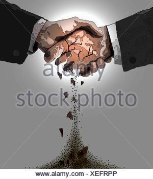 Close up of handshake crumbling - Stock Photo