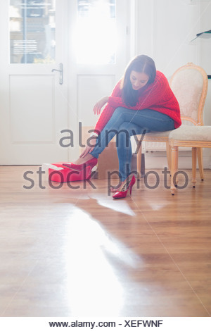 Full length of young woman trying on footwear in store - Stock Photo