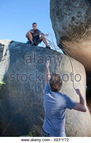 Young male climbers reaching out for each other on rock - Stock Photo