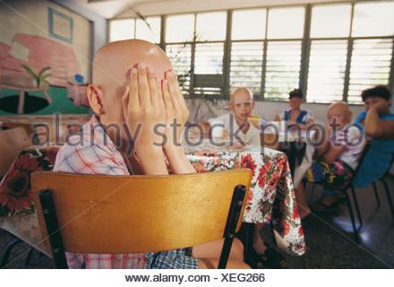 Victim of Chernobyl disaster boy covering his face in skin cancer hospital, Tarara, Havana, Cuba - Stock Photo
