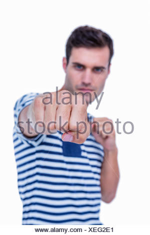 Handsome hipster attacking with his left fist - Stock Photo