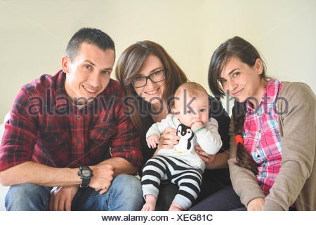 Happy portrait of two women, one man and a baby - Stock Photo