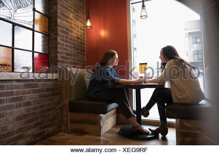 Affectionate mother and daughter talking, holding hands at diner booth - Stock Photo