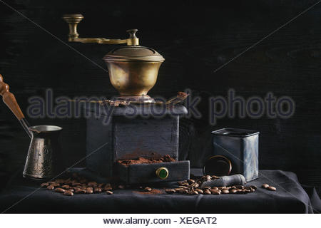 Old vintage grinder with roasted coffee beans and grind coffee in tin jar with scoop over black table with black wooden background. Dark still life - Stock Photo